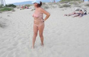 Naturist elderly chick on public beach